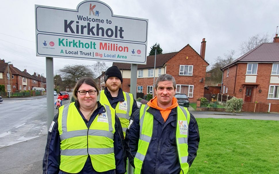 Three rangers, Coriena, Michael and Phil, stand by a sign to Kirkholt.