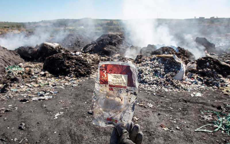 A hand holding up Tesco cheese plastic packaging with burning rubbish heaps in the background.