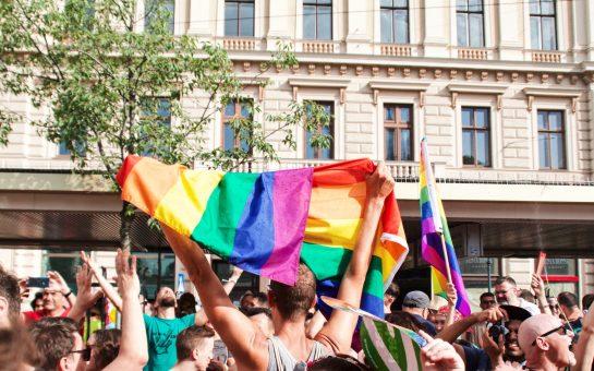 Man holding LGBT pride flag in crowd