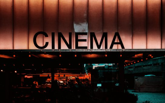 A photograph of the front of a cinema lit up with fluorescent lights